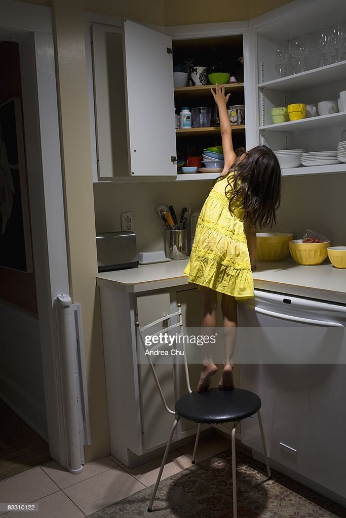 Girl Standing On Chair Reaching Into Cabinet Stock Photo
