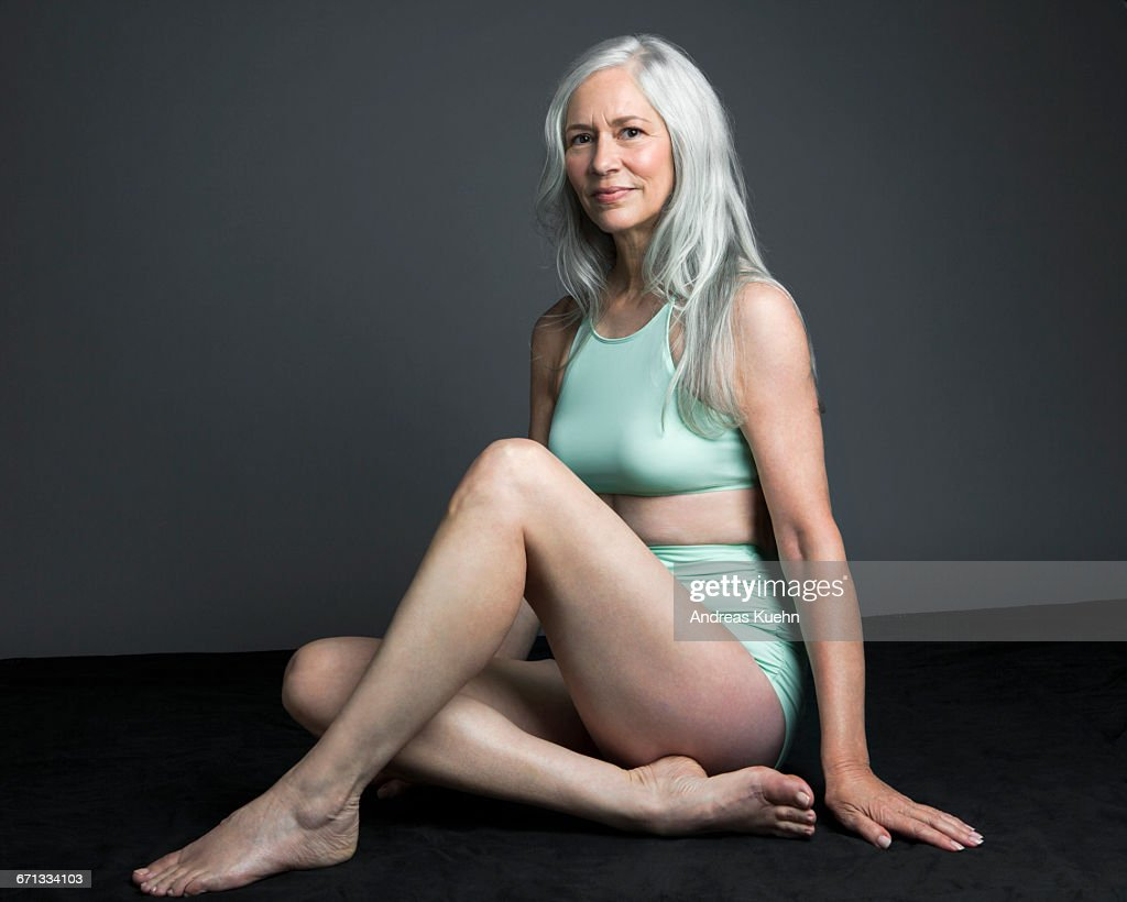 Grey Haired Woman In Swimsuit Sitting Down Stock Photo