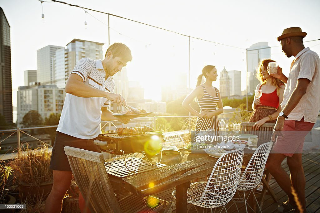 Group Of Friends Having Drinks On Rooftop Deck High-Res Stock Photo - Getty Images