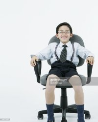 Happy Little Boy Sitting On Office Chair Stock Photo