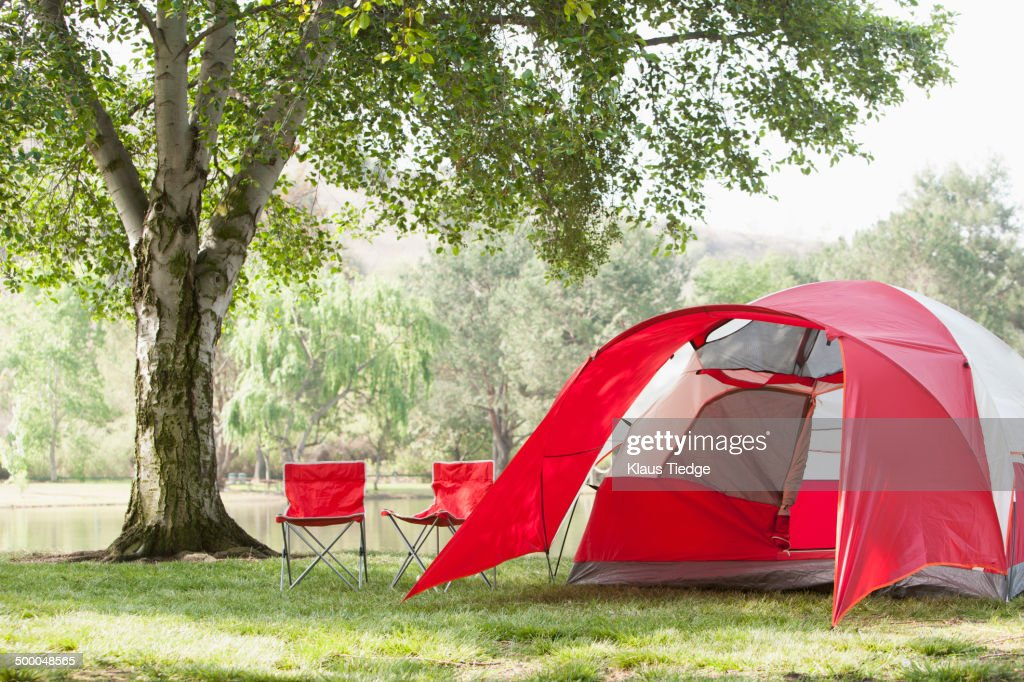Lawn Chairs And Tent At Campsite Stock Photo