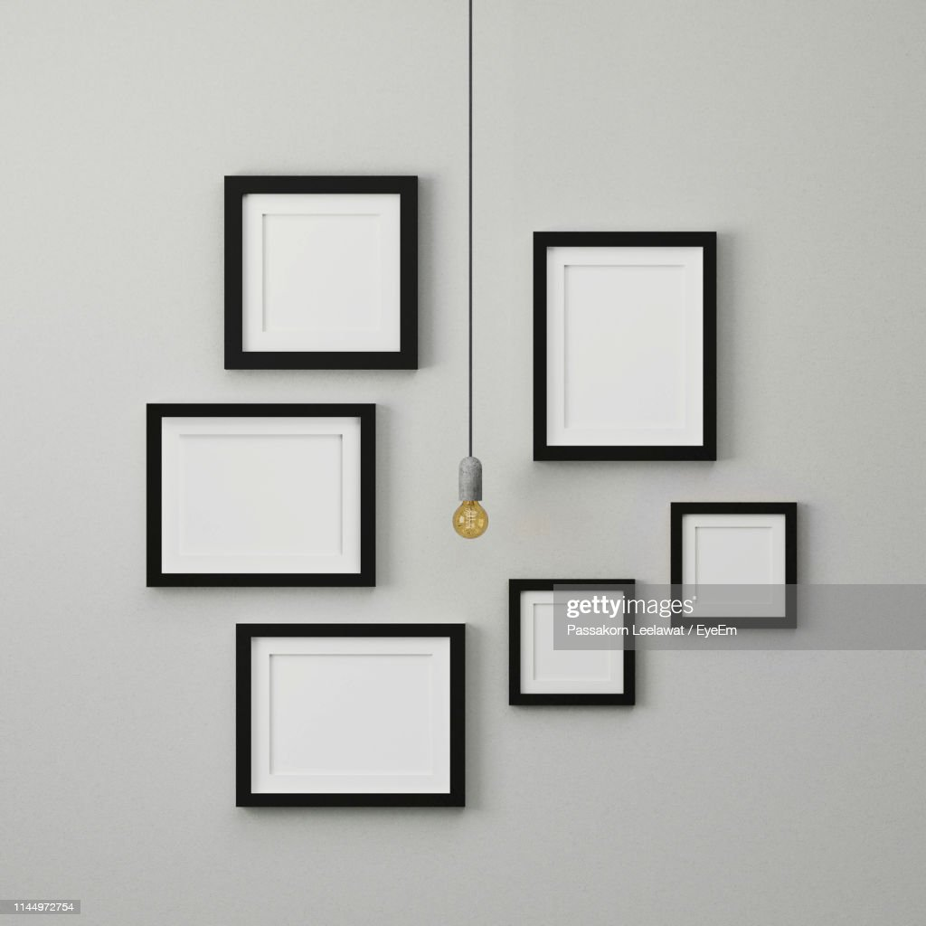 light bulb hanging by empty picture frames on white wall high res stock photo getty images