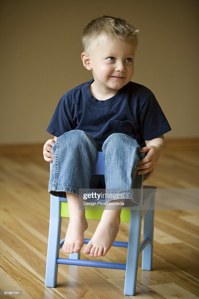 Little Boy Sitting On A Chair Stock Photo