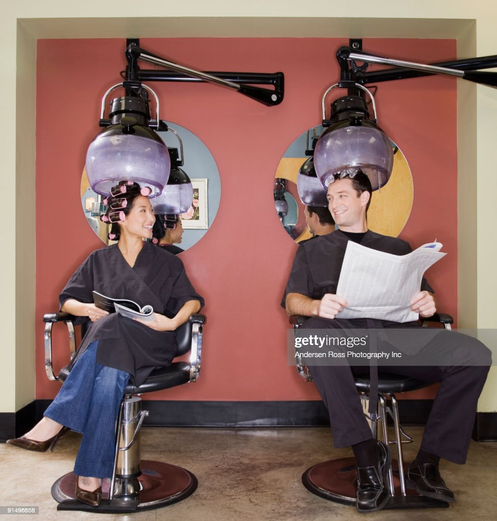 Man And Woman Under Hair Dryers In Salon Stock Photo