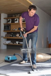 Man Cleaning Living Room With Vacuum Cleaner Stock Photo