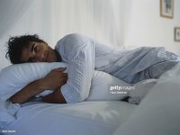 Man Hugging Pillow In Bed Stock Photo | Getty Images