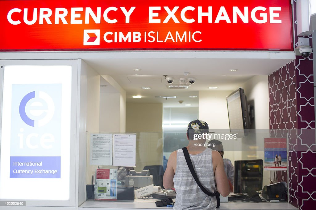 A man stands at a CIMB Group Holdings Bhd. currency exchange kiosk at... News Photo - Getty Images