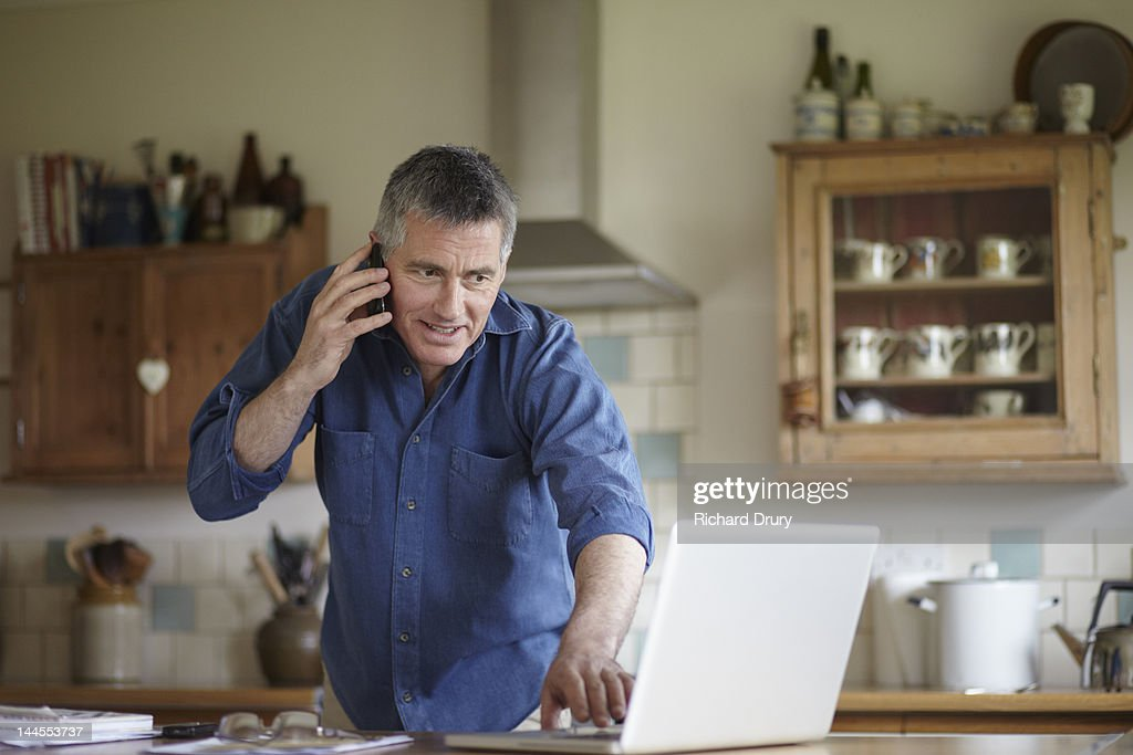 kitchen phone islands that look like furniture man using and laptop in stock photo getty images