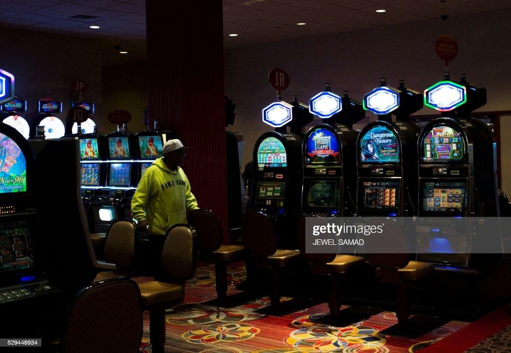 A Man Walks Past Slot Machines At A Near Empty Part Of A