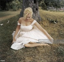 Marilyn Monroe Poses Sitting In Grass Barefoot