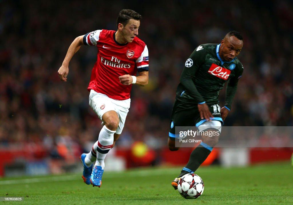 Mesut Oezil Of Arsenal Goes Past Camilo Zuniga Of Napoli