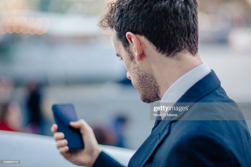 Over The Shoulder View Of Businessman Texting On
