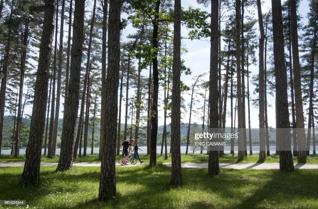 People Walk Along The Banks Of The Saint Ferreol Lake A