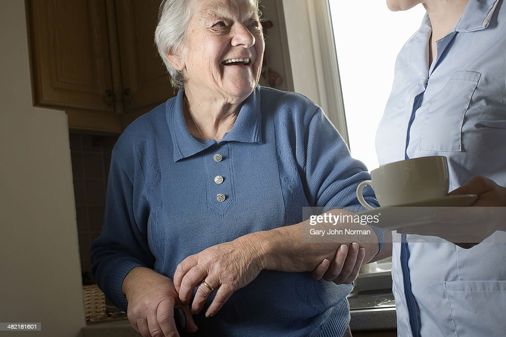 Personal Care Assistant Carrying Cup Of Tea For Senior