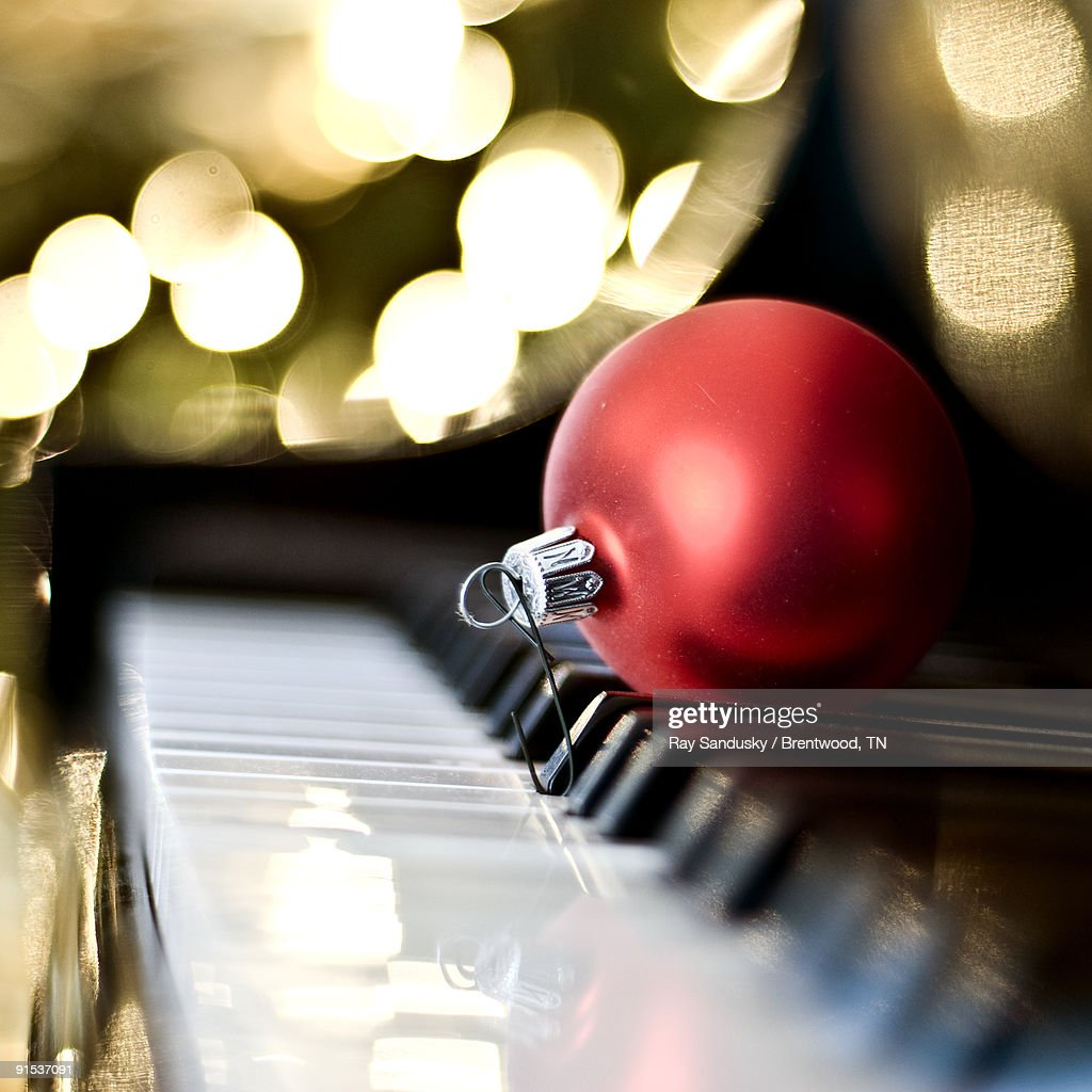 Piano Keyboard With Red Christmas Tree Ornament Stock
