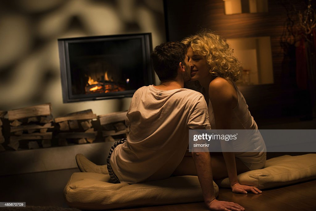 Couple Relaxing In Front Of Fireplace Man Looking At Woman Stock Fireplace Couple Stock Photos And Pictures | Getty Images