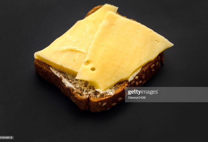 Sandwich On Black Bread With Cheese And Butter Stock Photo Thinkstock