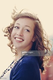 smiling girl with curly hair blowing