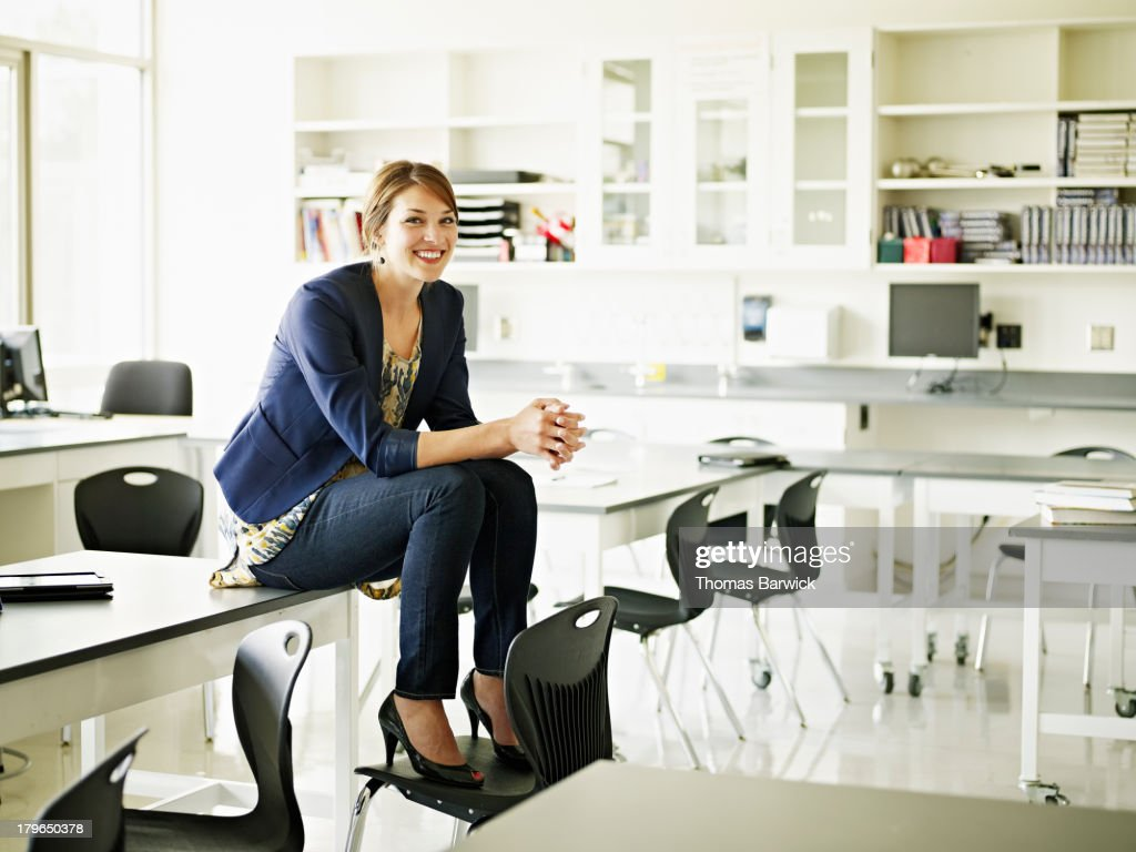 Smiling Teacher Sitting On Desk In Classroom Stock Photo