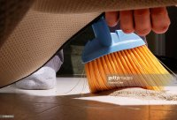 Sweeping Dirt Under The Carpet Stock Photo