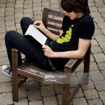 Teen Boy Reading Book In Wooden Chair Exterior High Res Stock Photo Getty Images