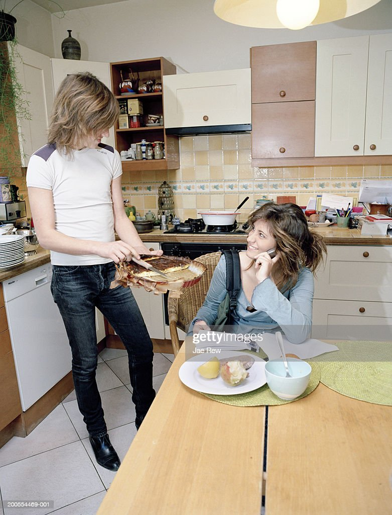 kitchen phone stainless steel cabinets manufacturers teenage girl sitting in on table using mobile boy standing