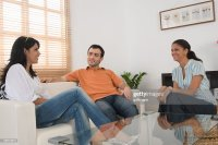 Three Friends Talking In The Living Room Stock Photo