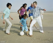 Three Generation Group Playing Football Beach Stock