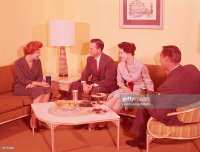 Two Couples Sitting Around Coffee Table In Living Room ...