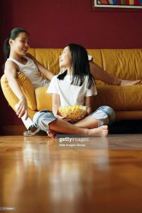 Two Sisters Sitting In Living Room Talking Stock Photo