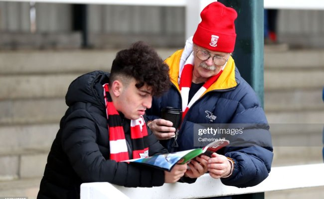 Two Woking Fans Read The Match Day Programme Prior To The