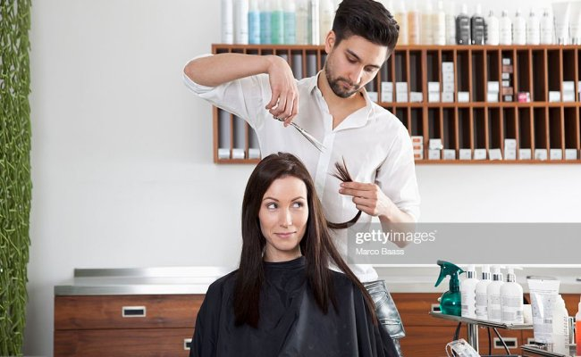 A Woman Having Her Hair Cut By A Male Hairdresser High Res