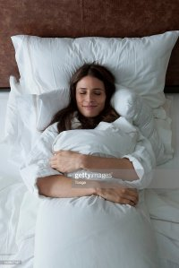 Woman In Bed Hugging Pillow Stock Photo | Getty Images