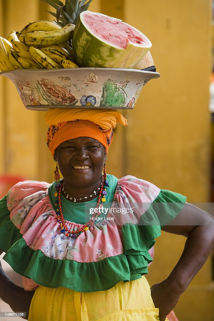 Woman In Colourful Traditional Attire Carrying Bowl Of
