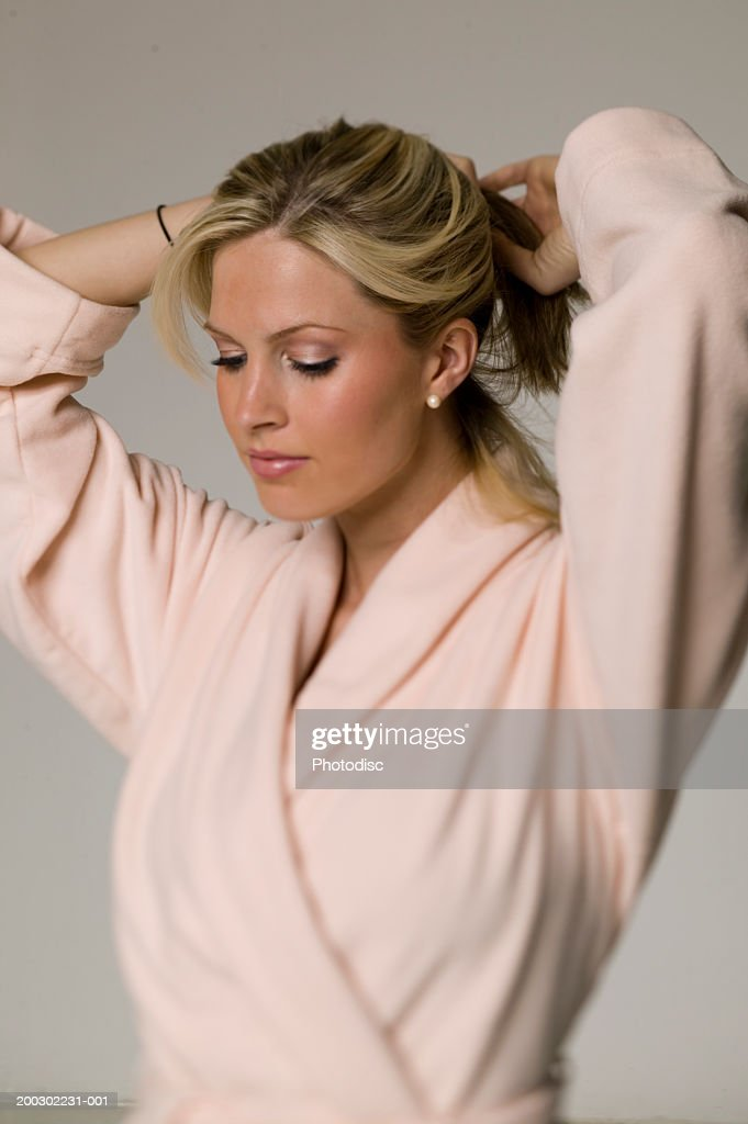 woman in dressing gown fixing hair