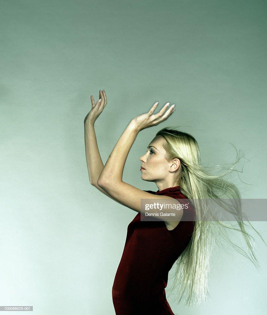 woman raising arms in air hair