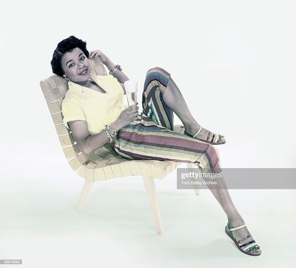 Chair Pants A Woman Wearing A Yellow Blouse Striped Pants And Sandals