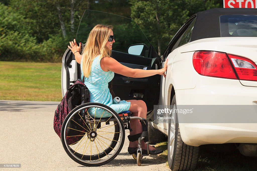 used wheel chair human touch massage replacement parts woman with spinal cord injury in wheelchair accessing her adaptive vehicle stock photo | getty ...
