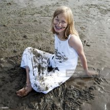 Young Girl Sitting In Mud Flats Stock Getty