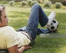 Young Man Lying Grass Holding Football