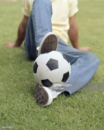 Young Man Sitting Grass With Football Feet