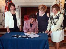 Senator Gayle Goldin (left) attends a bill signing with Rhode Island Governor Gina Raimondo (center).
