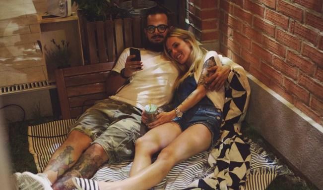 Par romântico no quintal, sentado na grama e assistindo suas fotos na tela grande.