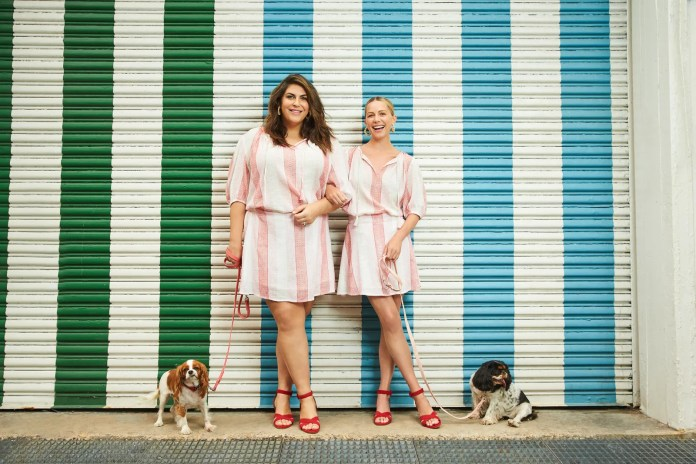 two women wearing the same short dress next to dogs on leashes