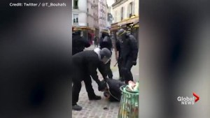 French president's aide seen in police helmet beating man during May Day protest