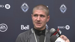 Whitecaps coach Carl Robinson plays on the pitch alongside players