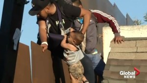 Migrant caravan: Father and baby detained after climbing Tijuana border fence