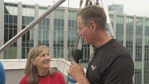 Chris Gailus steps over the side of the Guinness Tower for Easter Seals