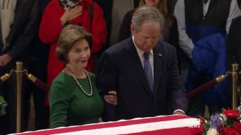 Bob Dole, 95, gets out of his wheelchair for moving salute to George