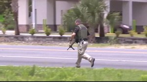Police take cover behind vehicle as shots ring out during active shooter situation in Panama City, Florida